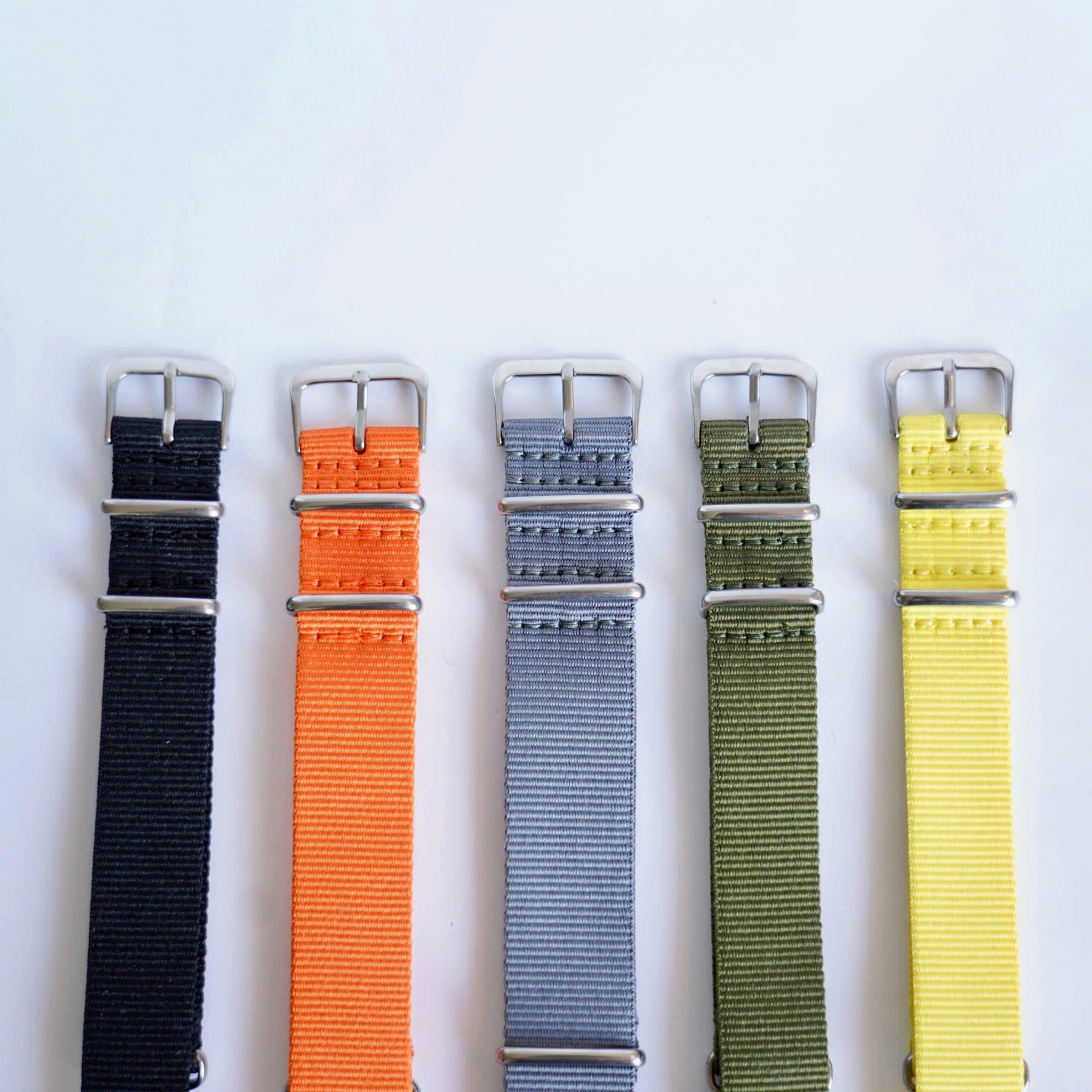 Natoreimer i svart, oransje, blå/grå, grønn og gul med sølvfarget spenne